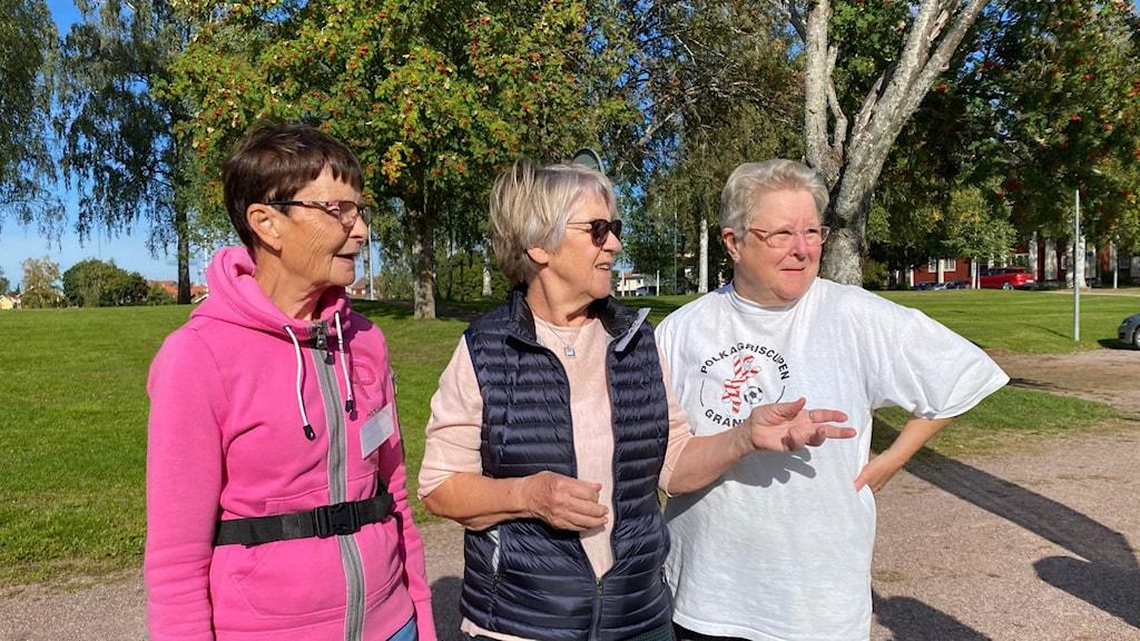 Tre äldre kvinnor i solskenet.