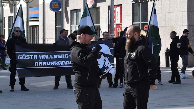 Svartklädda personer från nazistiska Nordiska motståndsrörelsen.