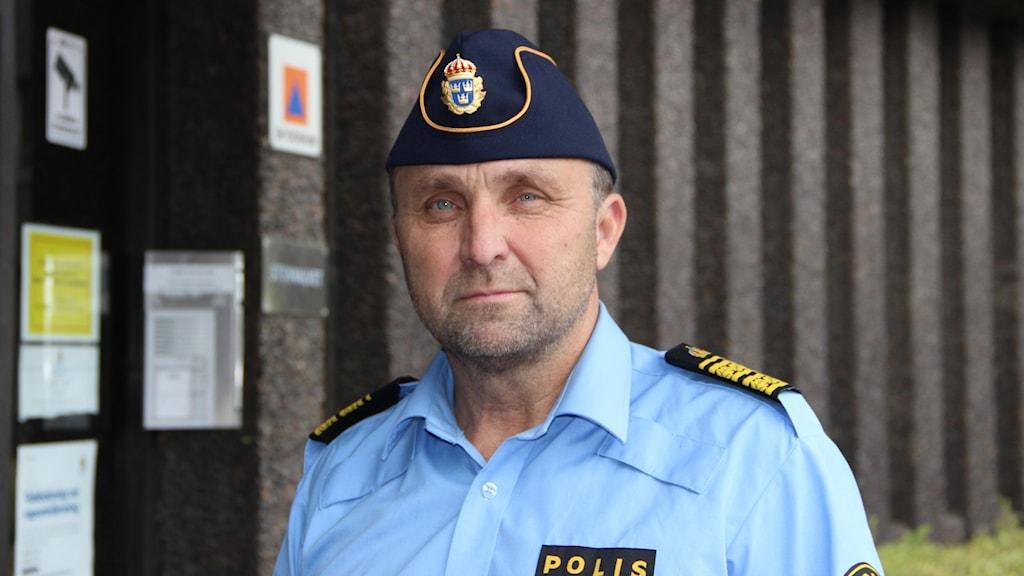 Fotot visar en man i polismössa framför polishuset.
