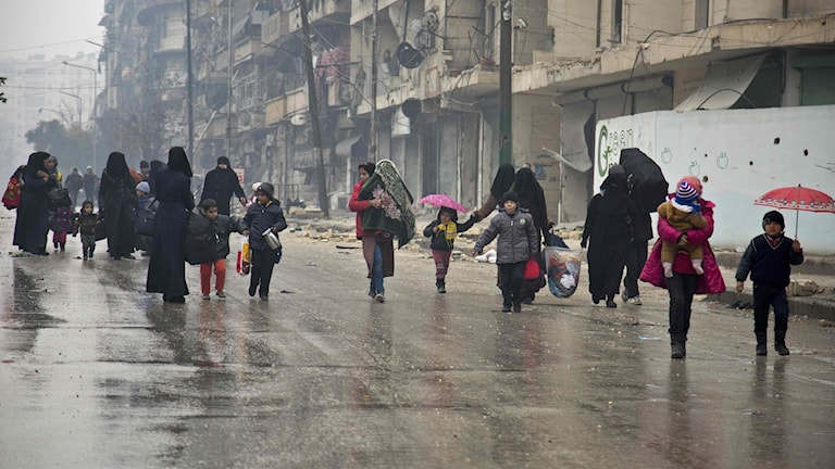 Människor går på en gata i en krigshärjad stad och bär barn och tillhörigheter.