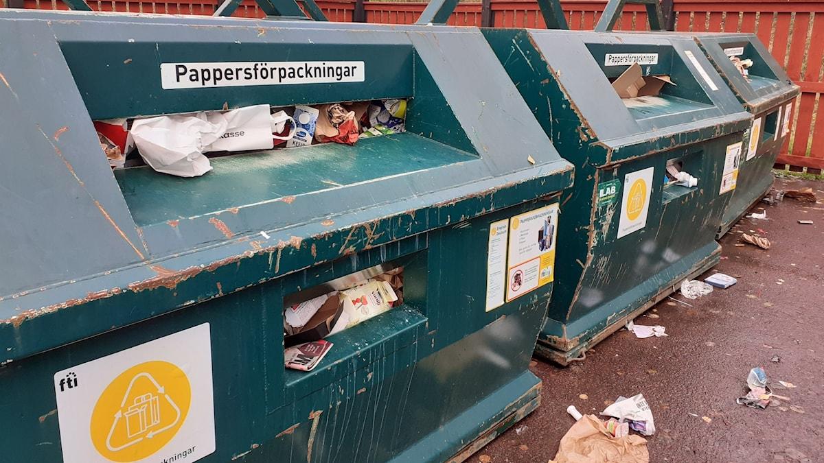 Fulla behållare för pappersförpackningar och skräp på marken.