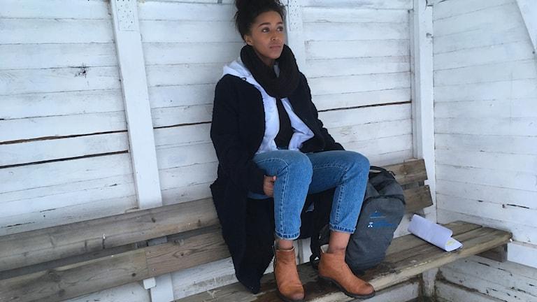 Sheyma Sheikhnur sitter på en bänk vid en idrottsplats.