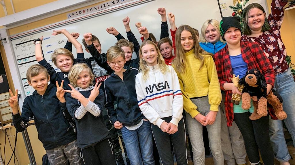 En skolklass i ett klassrum som sträcker upp händerna och är glada.