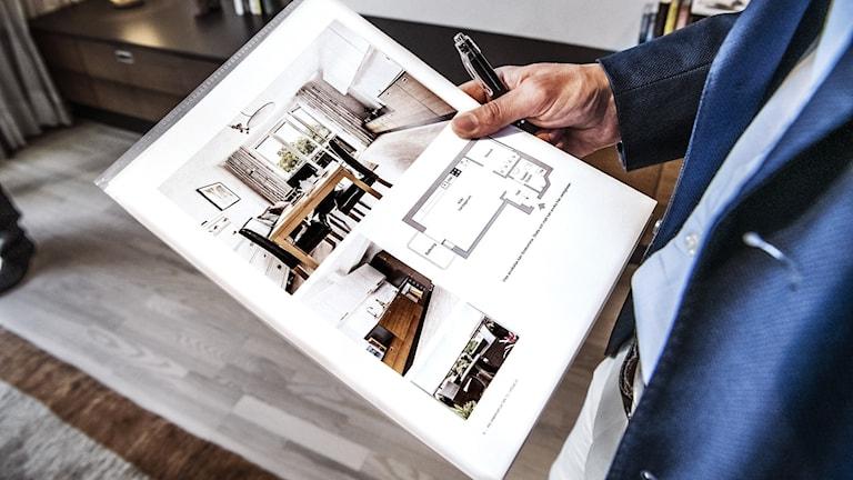 En man i kostym håller i ett papper med en planritning över en bostadsrätt.