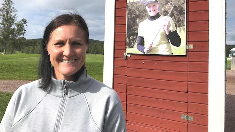 Golfspelaren Mimmi Hjorth från Aspeboda står vid ett rött hus med vita knutar med en golfbana i bakgrunden.