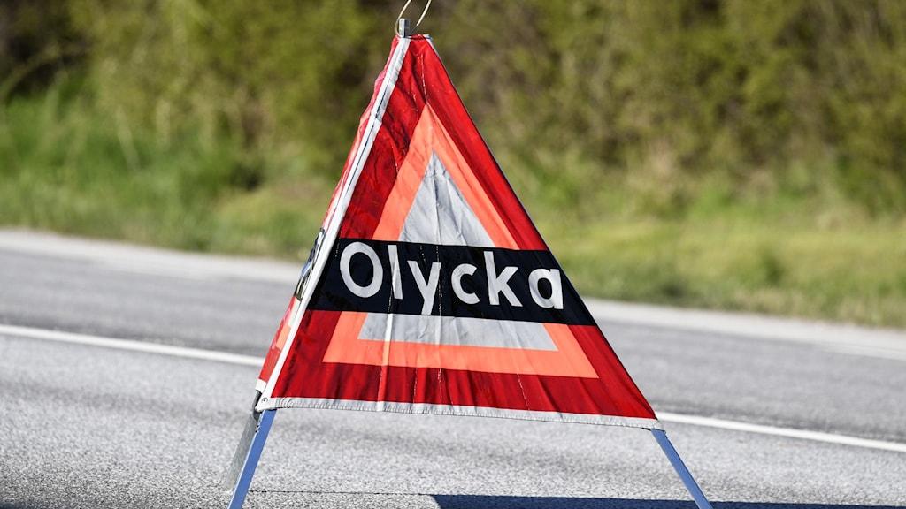 Varningstriangel med texten Olycka står på en väg.