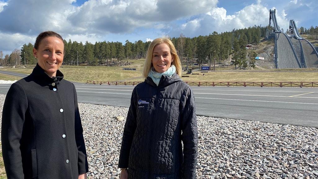 Två kvinnor i mörka kläder och glad min står framför en skidstadion med backhoppningsbackar i bakgrunden.