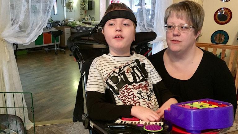 En kvinna och en pojke sitter vid ett bord.