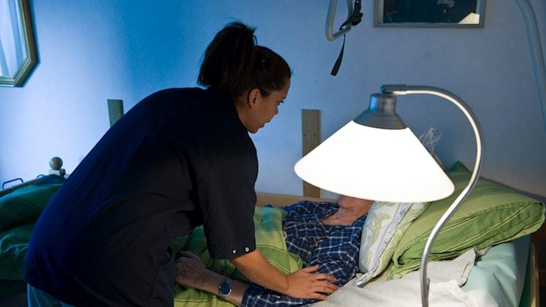 En undersköterska som bäddar ner en brukare i sängen.
