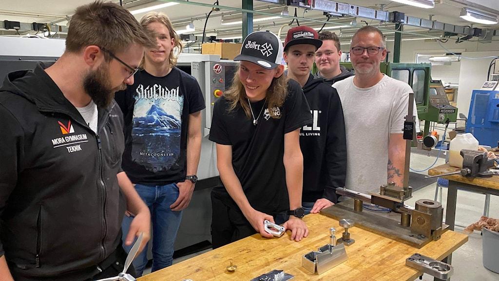 Elever och lärare på utbildningen i robot- och CNC-teknik på yrkeshögskolan i Mora står vid ett bord i en lektionssal och tittar på teknik- och robotprylar. Mannen i långt hår och keps heter Emanuel Ädling.