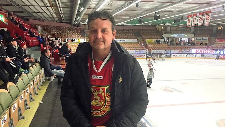 En man i svart jacka och röd tröja med Mora IK:s klubbsymbol på, stående på läktaren i en ishall och bakom ser man både åskådare och på isen ishockeyspelare.