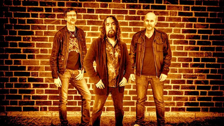 Tre medlemmar i bandet Winding Road står mot en tegelvägg.