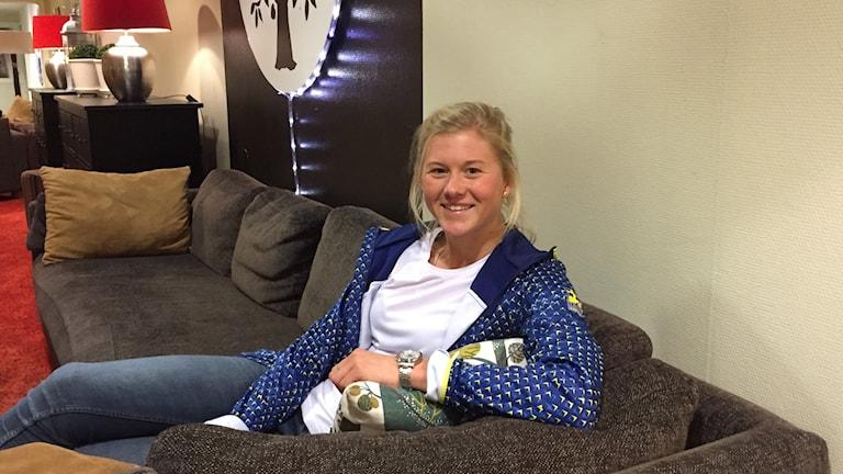 Skidåkaren Maja Dahlqvist sitter i en grå soffa och tittar in i kameran.