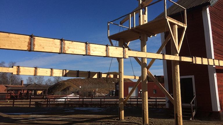 Två träkonstruktioner i luften som går mellan ett hjulhus och hissanordningen till gruvan i ett annat hus.