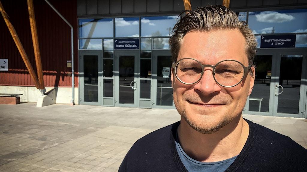 Man med glasögon framför tegera arena