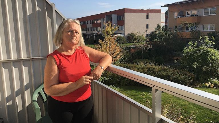 Lisen Bjurström står på balkongen med ena armen på räcket och ser allvarlig och smått bekymrad ut.