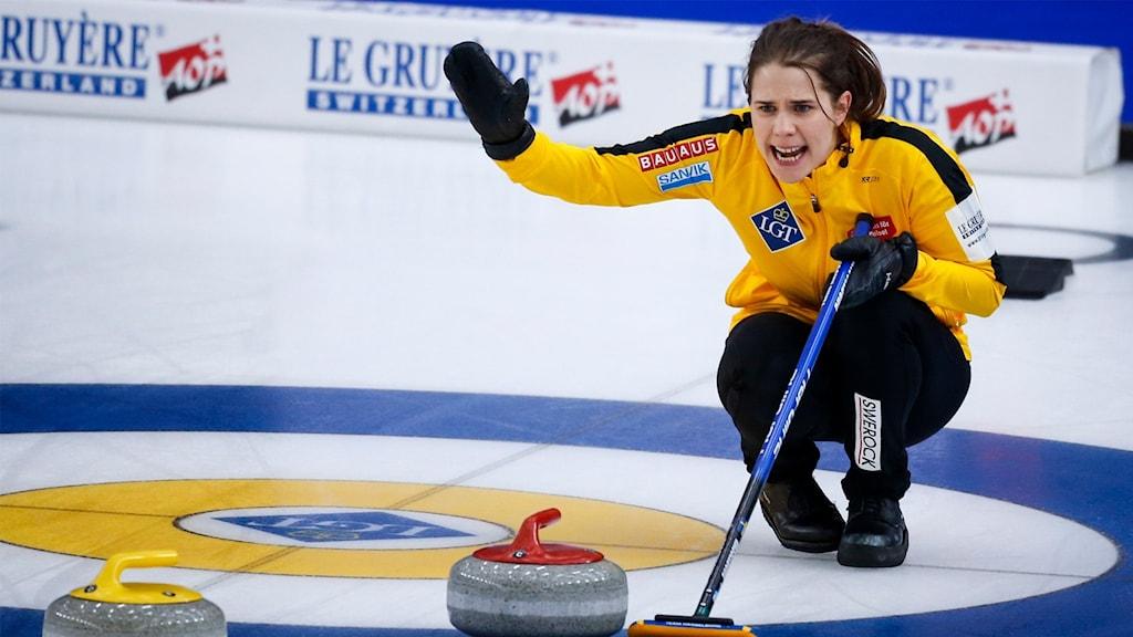 Kvinna sitter på isen och höjer handen - curling