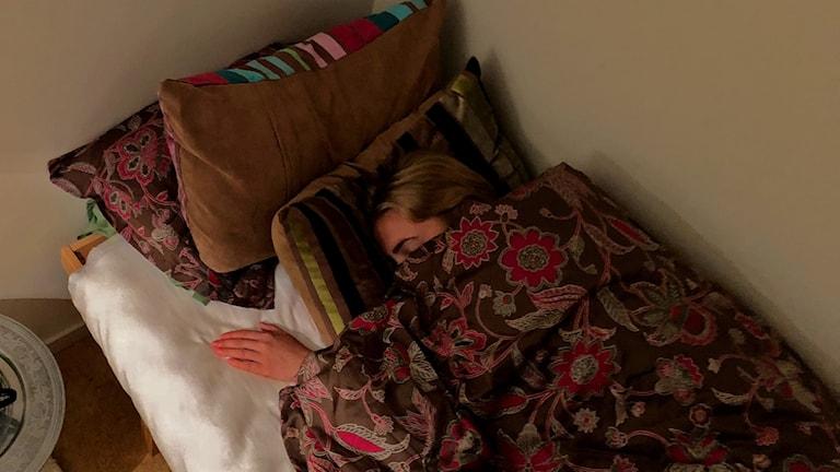 En person som ligger i en säng och sover.