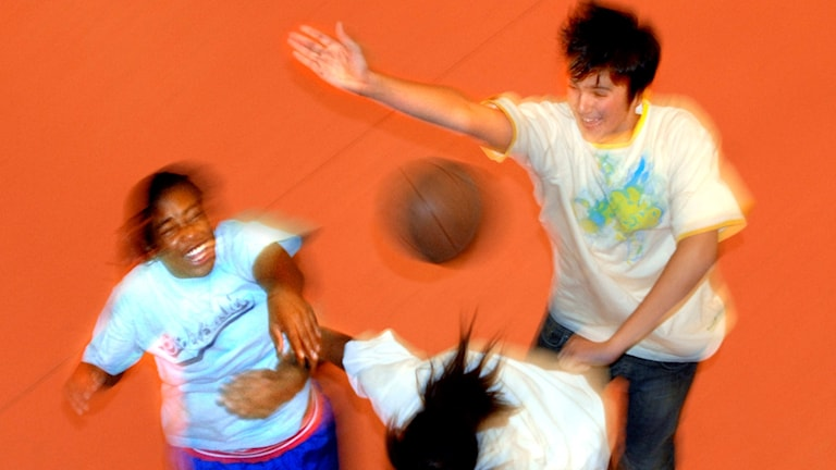 Tre ungdomar som spelar basket
