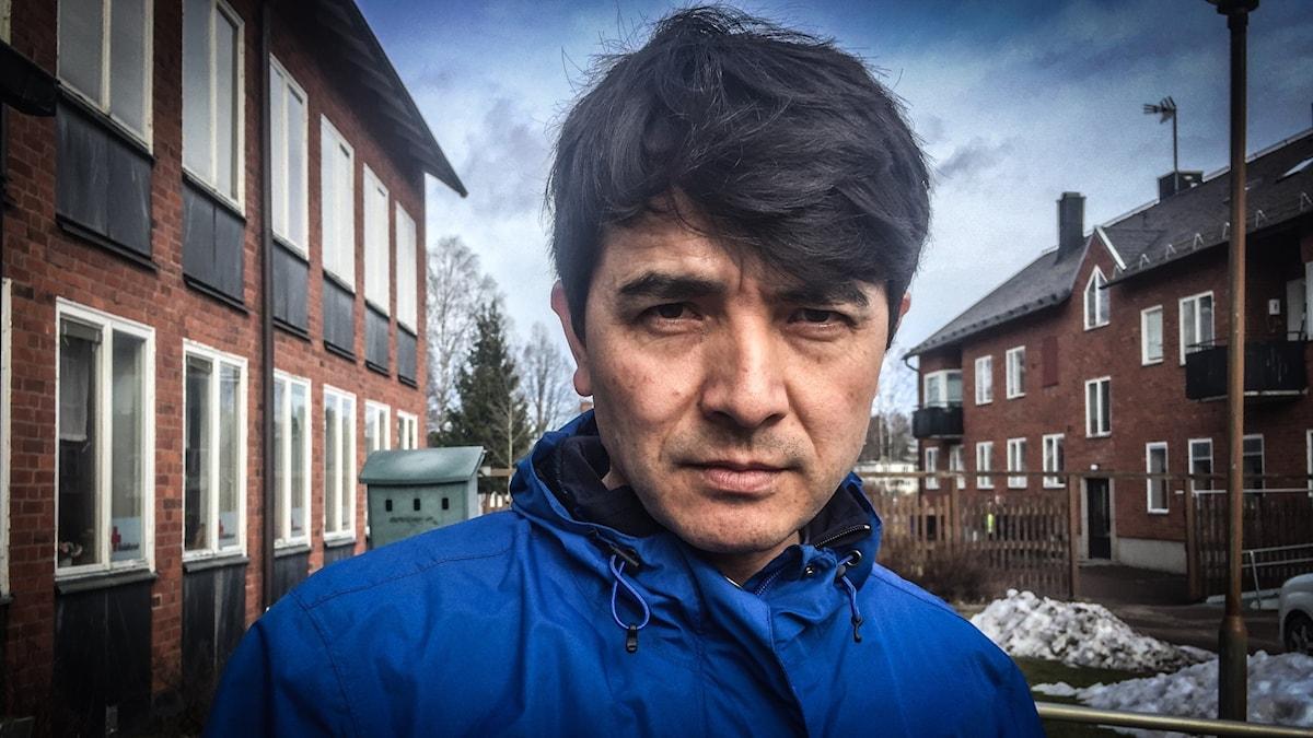 En man med svart hår och blå jacka tittar allvarligt rakt in i kameran. På båda sidor om honom syns tegelhus.