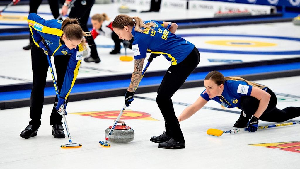Sofia Mabergs och hennes lagkamrater sopar isen framför en curlingsten.