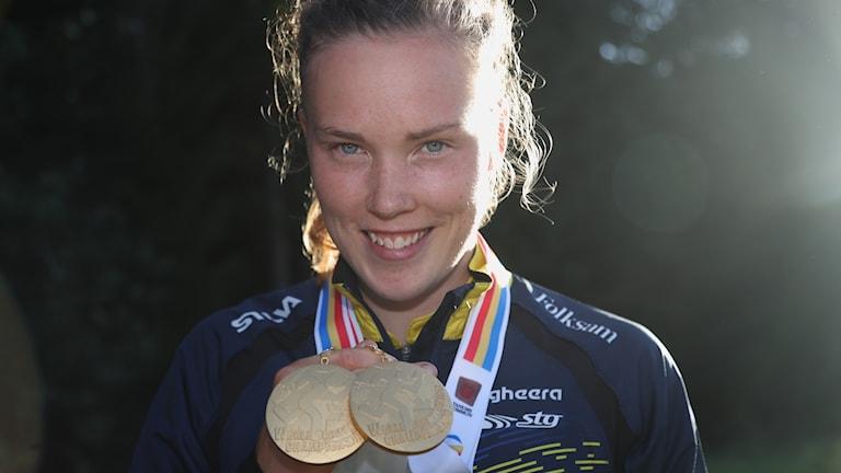 Närbild på en glad tove Alexandersson som håller upp två guldmedaljer.