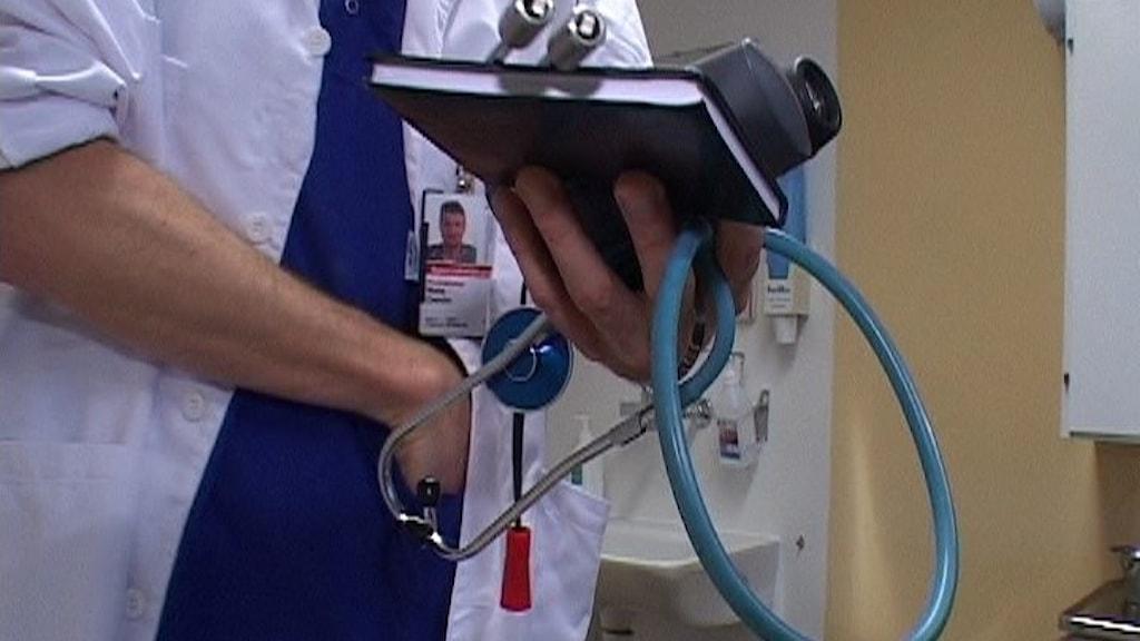 Närbild på en överkropp i vit läkarrock och med stetoskop och block i händerna.