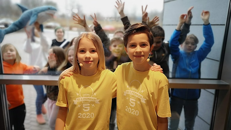 två elever står och håller om varandra medan klasskompisarna står i bakgrunden.