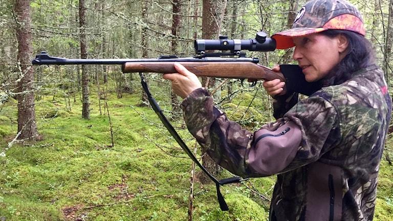 Anette Eklund från Bjursås står i skogen med sin bössan