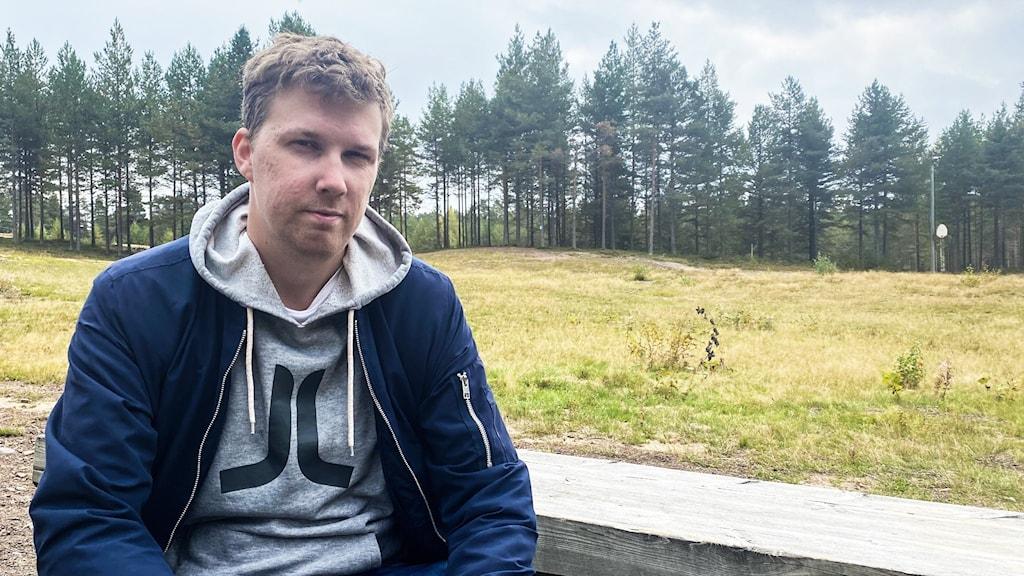 En man sitter på en bänk framför en glänta i en skog.