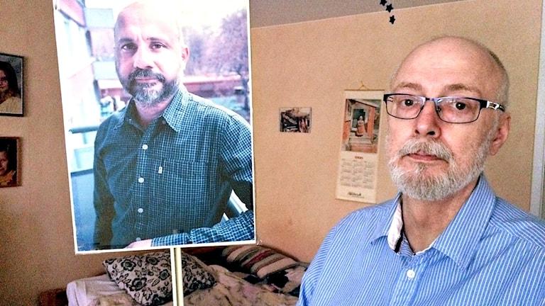 En man håller upp en skylt med bild på en annan man.