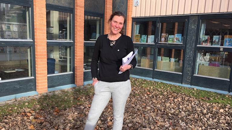 En kvinna står framför en byggnad med böcker i fönstren. Hon ler och har ena handen i fickan och håller med den andra en trave papper.