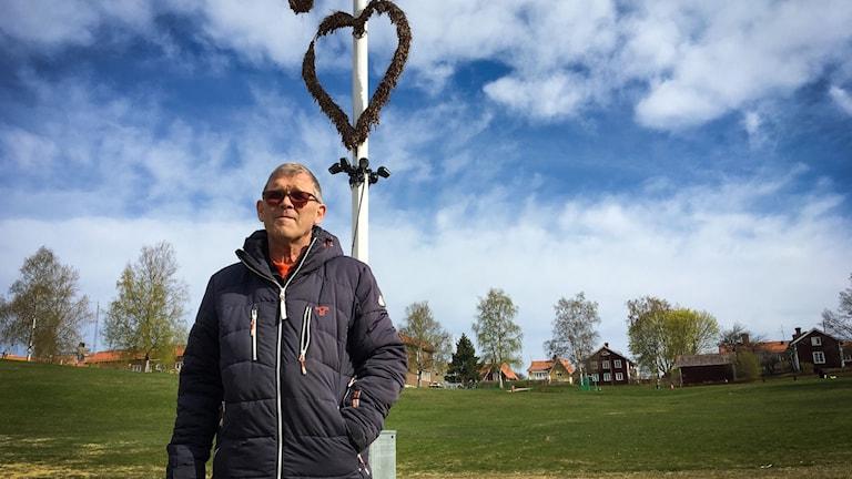 Anders Tull står iklädd jacka vid den hjärtprydda majstången i Gropen i Leksand där det brukar vara stort midsommarfirande varje år.