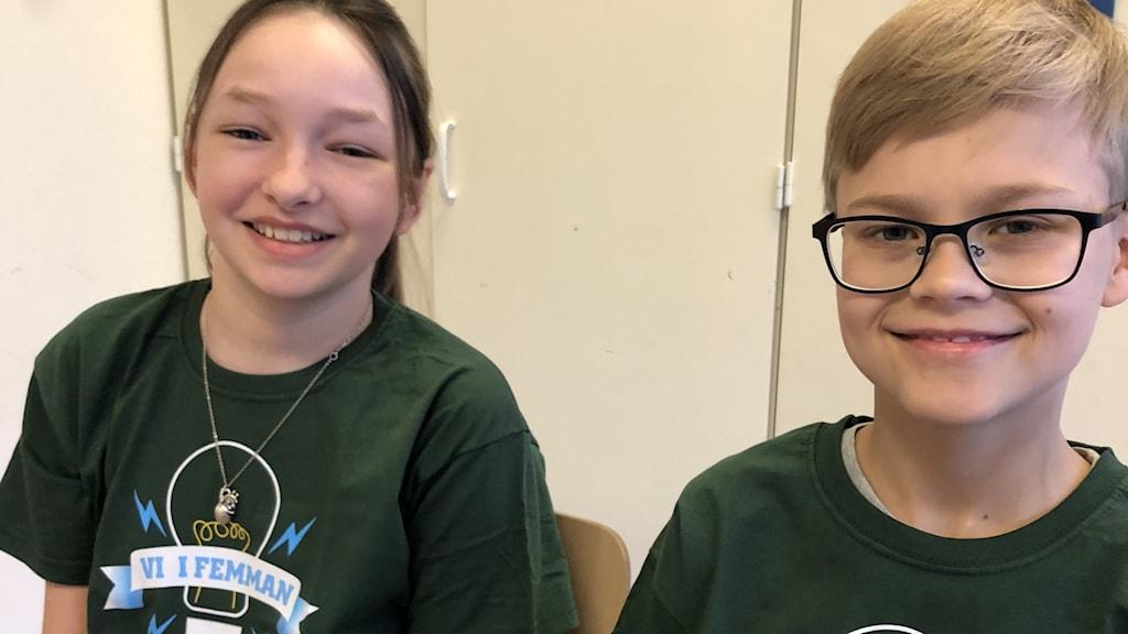 En pojke med glasögon och en flicka i gröna tröjor.