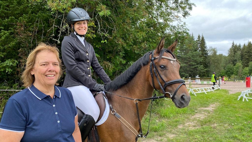 På fotot syns ryttaren Therese Sandgren. Hon sitter på sin häst och är klädd i en kavaj och vita ridbyxor. Bredvid hästen står Eva Hammar, som är klädd i en pikétröja.