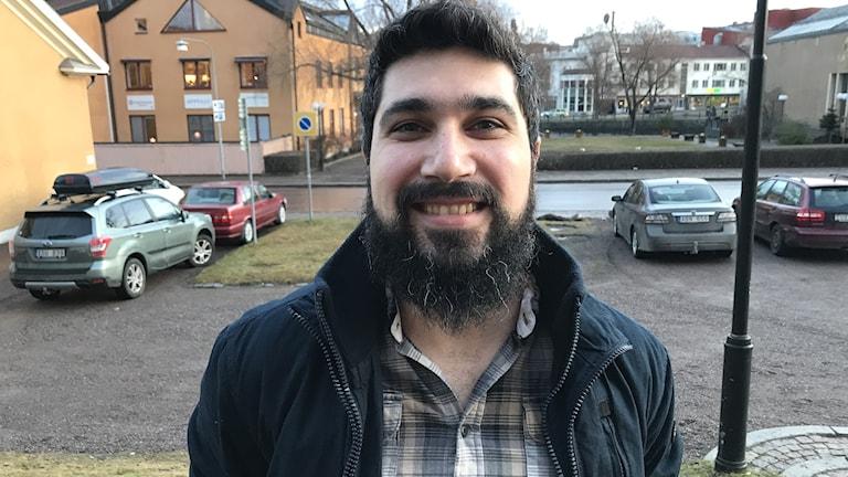 Bashar Mustafa, från Irak men boende i Mora, startar eget företag för att hjälpa företag med integrationsfrågor och invandrare att lära sig den svenska företagskulturen. Bilden visar en man i skägg, skjorta och jacka som står utomhus på en parkering.