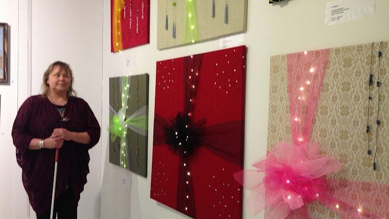 Annelie Larsson framför sina tavlor