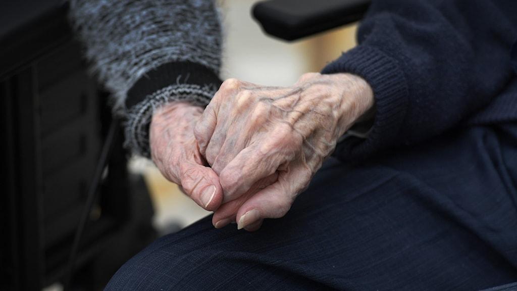 Två äldre som håller varandra i handen.