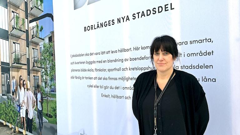 Pernilla Bergkvist står i svarta kläder framför en stor affisch/vägg med texten Borlänges nya stadsdel, samt en skiss över hur de nya bostadsrätterna ska se ut när de är klara.