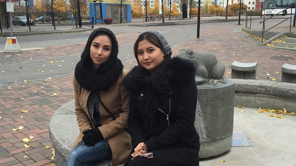 Två tjejer sitter i stadsmiljö och ser allvarligt in i kameran.