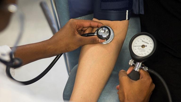 En läkare som tar blodtryck på en patient,