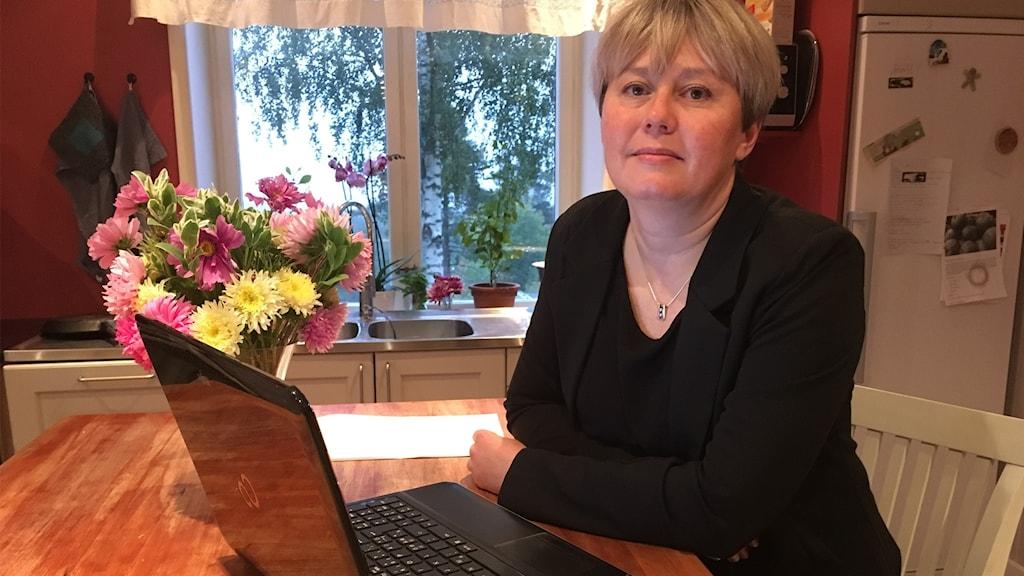 Eva Carlsson sitter vid ett köksbord med en dator framför sig