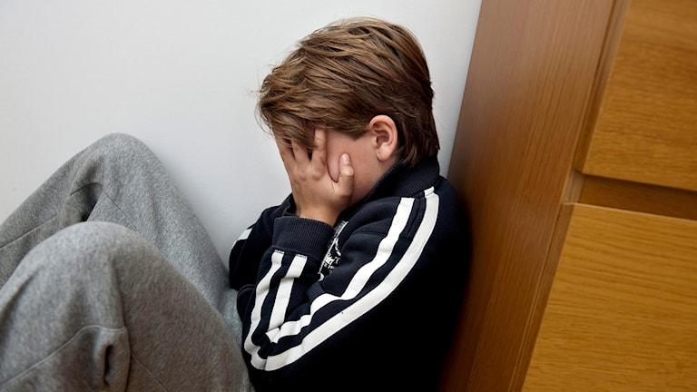En ledsen pojke sitter på golvet i ett hörn med händerna för ansikte