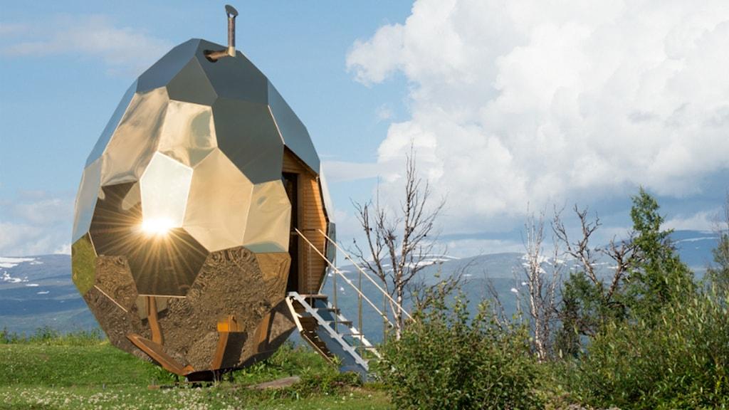 Det guldfärgade ägget är en bastu och rymmer åtta personer. Ägget står på ett fjäll.