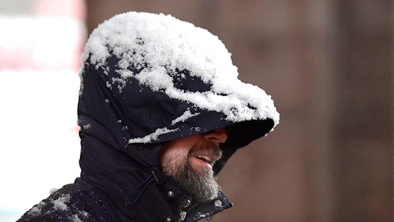 En man med en snöig luva.