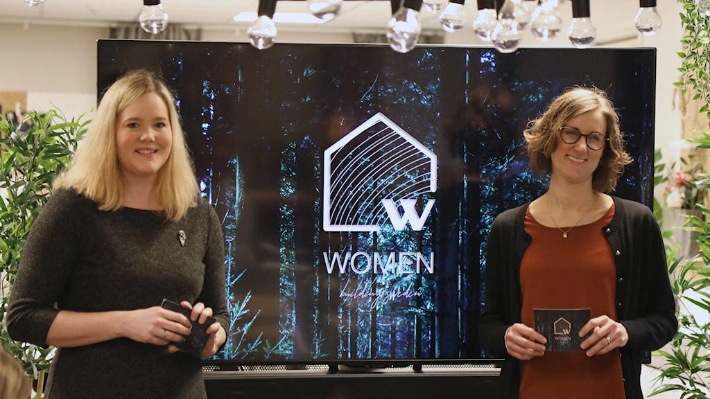 Två kvinnor står framför en stor skärm.