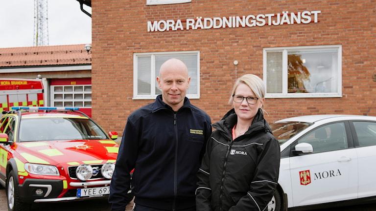 En man och en kvinna framför en brandbil och en hemtjänstbil och en tegelvägg med texten Mora räddningstjänst.