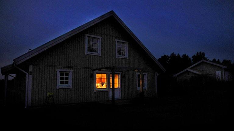 Hus i mörker med ett upplyst fönster.