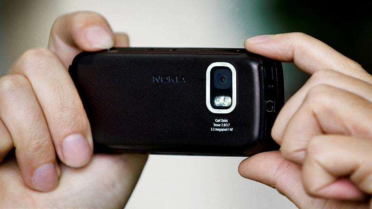 Två händer håller i en mobilkamera.