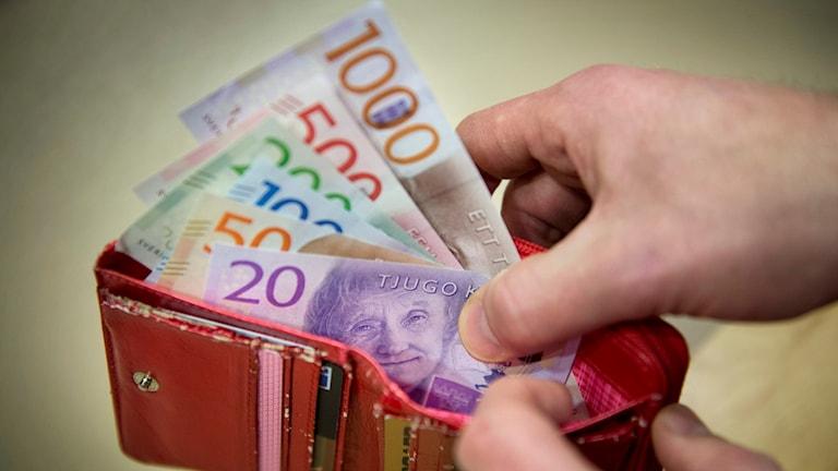 En person som tagit upp ett antal sedlar ur sin röda plånbok.